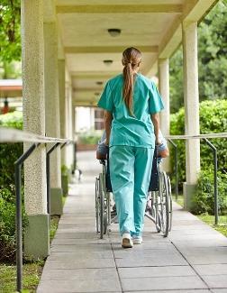 nurse transporting patient in wheelchair